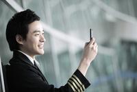 スマートフォンを操作するパイロット 02442000624| 写真素材・ストックフォト・画像・イラスト素材|アマナイメージズ