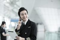 タブレットPCを持って携帯電話するパイロットと客室乗務員 02442000638| 写真素材・ストックフォト・画像・イラスト素材|アマナイメージズ
