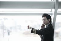 時計を見て電話している乗務員 02442000677| 写真素材・ストックフォト・画像・イラスト素材|アマナイメージズ