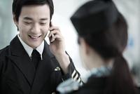 スマートフォンで話す乗務員 02442000682| 写真素材・ストックフォト・画像・イラスト素材|アマナイメージズ