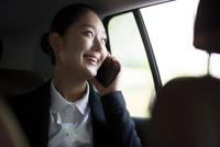 車内でスマートフォンで話すビジネスウーマン 02442000808| 写真素材・ストックフォト・画像・イラスト素材|アマナイメージズ