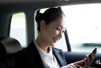 車内でスマートフォンを操作するビジネスウーマン 02442000809| 写真素材・ストックフォト・画像・イラスト素材|アマナイメージズ