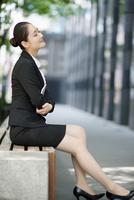 ベンチに座っているビジネスウーマン 02442000847| 写真素材・ストックフォト・画像・イラスト素材|アマナイメージズ