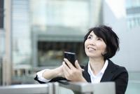 スマートフォンを操作している中年の女性 02442001109| 写真素材・ストックフォト・画像・イラスト素材|アマナイメージズ