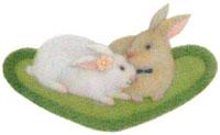 ハート型の芝生の上のうさぎのカップル