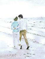 海辺の砂浜を歩くカップル