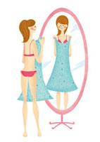 鏡の前でワンピースを合わせる女性