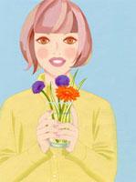 花をグラスに入れて持っている女性