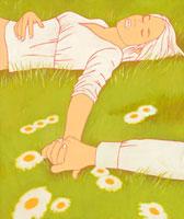 野原で手をつないで横になっている女性