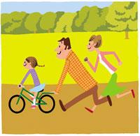 自転車の練習をする少女と両親