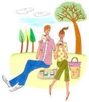 芝生でサンドイッチを食べるカップル