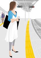 駅で電車が来るのを腕を組んで待つ女性