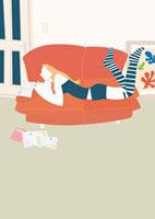 ソファに寝そべって雑誌を見る女性