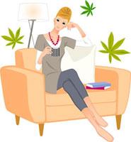 ソファに座ってコーヒーを飲んでいる女性