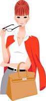 赤いカーディガンを羽織りメガネを持つ女性