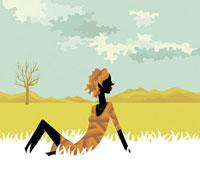 草原に座るワンピースを着た女性