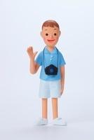 カメラを提げて、右手を上げている水色の半袖シャツを着た男の子