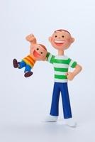 少年と腕にぶら下がる小さい男の子 02463000686| 写真素材・ストックフォト・画像・イラスト素材|アマナイメージズ