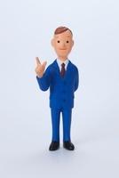 青色のスーツを着て右人差し指をたてている男性正面