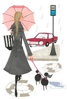 雨の中、犬と散歩している女性