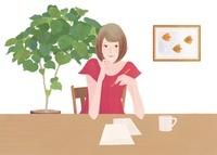 テーブルで座りながら手紙を書いている女性
