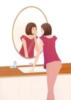 鏡を見ながら自分の顔を見ている女性