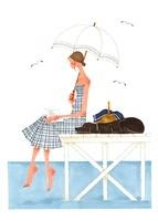 犬と海で日傘を差しながら本を読んでいる女性