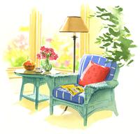 ピンクの花が入った花瓶が乗ったテーブルとアームチェア