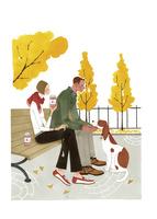 秋の公園でベンチに座る男性と女性と犬