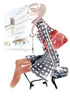 バッグを肩にかけベンチにすわる女性