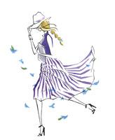 風で帽子が飛ばないように抑えて歩く女性