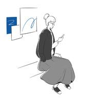 ベンチに座ってスマートフォンを操作する女性