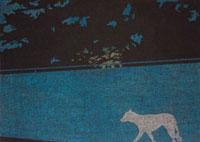 夜の樹木に覆われた高い塀の前をうろうろする犬