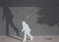 嵐で樹木も揺れる夜に高い壁の前をうろつく男性