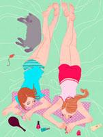 ベッドの上でマニキュアを塗る二人の女性