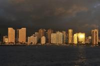 海上から望む夕日に染まるホノルルの街