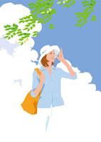 真夏の空の下爽やかな風を受ける女性