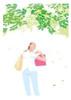 光あふれる緑の葉の中の女性