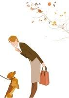 秋の枯れ葉の中、散歩中の犬とじゃれる女性