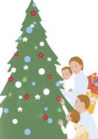 クリスマスツリーに飾りをするファミリー