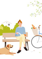 街の公園のベンチで本を読む買い物帰りの女性