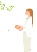 新緑の下に佇む本を読む女性
