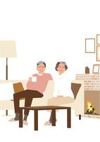 冬の暖炉のあるリビングでお茶するシニアカップル
