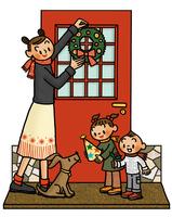 クリスマスリースをかける母親と子供とイヌ