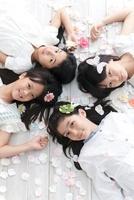 花びらに囲まれて床に寝そべる4人の女の子