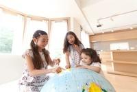 大きな地球儀を指差す3人の女の子