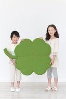 大きな四葉のクローバーのクラフトを持つ男の子と女の子