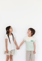 手をつないで上を見上げる男の子と女の子