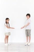 両手を前に差し出す男の子と女の子