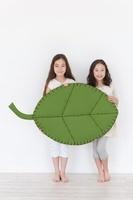 大きな葉のクラフトを持つ2人の女の子